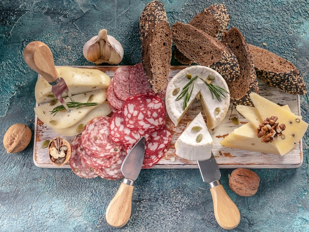Assorted sausages and cheese with bread on wooden board