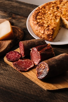 Assorted sausages near cheese and pie