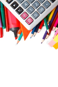 Assorted school supplies, including pens, pencils, scissors, glue and a ruler, on a white background