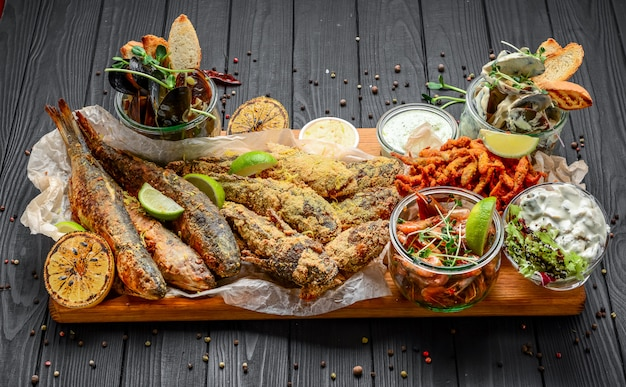 木製の表面のシーフードの前菜盛り合わせ、魚のフライ、ムール貝、エビ