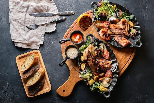 Ассорти из морепродуктов на тарелках. красивая композиция на сервированном столе из морепродуктов, кальмаров, креветок, стейка из лосося и осьминога. фото еды, сдержанная, традиционная итальянская кухня. вид сверху, сэкономьте место.