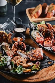 접시에 모듬 해산물. 제공된 해산물 테이블, 오징어, 새우, 연어 스테이크 및 문어에 대한 아름다운 구성. 음식 사진, 낮은 키, 전통 이탈리아 요리. 평면도, 공간 절약.