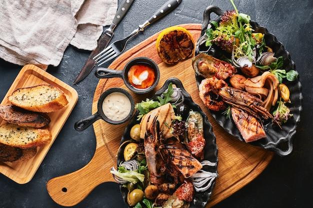 シーフード盛り合わせ。提供されるシーフードテーブル、イカ、エビ、サーモンステーキ、タコの美しい構図。