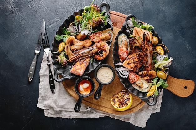 접시에 모듬 해산물. 제공된 해산물 테이블, 오징어, 새우, 연어 스테이크 및 문어에 아름 다운 구성.