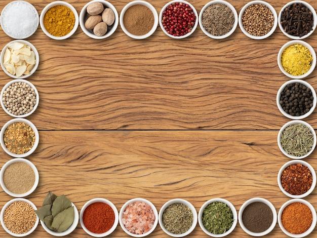 コピースペースの背景を持つ木製のテーブルの上の各種調味料とハーブ
