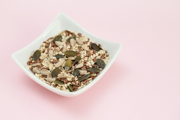 Assorted seeds in the small white bowl on pink table