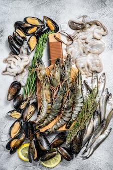 Assorted set of fresh seafood tiger prawns, shrimps, blue mussels, octopuses, sardines, smelt.