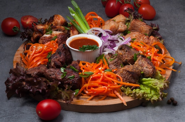 Assorted shish kebabs with carrots and tomato sauce on a wooden board