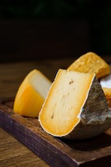 Ассорти из нарезанных сырных головок на разделочной доске на деревянном столе. сыроварня и сырный цех. натуральные фермерские молочные продукты. реклама и меню.