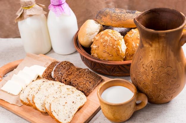 Ассорти из нарезанного полезного цельнозернового хлеба, сыра и молока на обед в пабе или ресторане со свежеиспеченными булочками в миске сзади