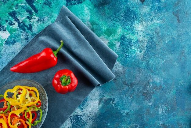 青の背景に、布片の赤唐辛子の横にあるボウルにスライスした唐辛子の盛り合わせ。