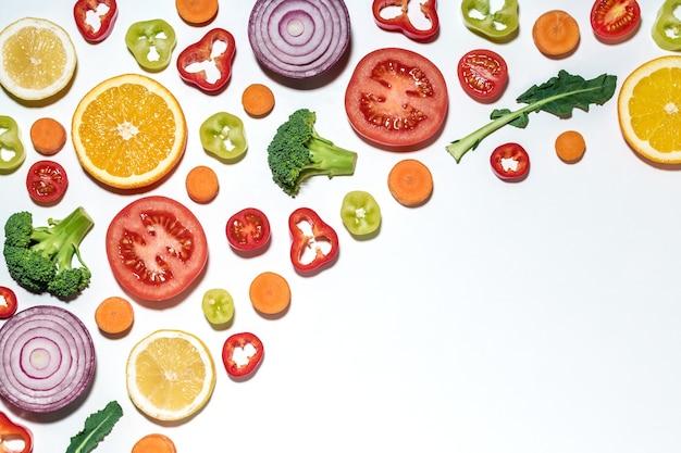 Ассорти из нарезанных овощей и фруктов на белой поверхности.