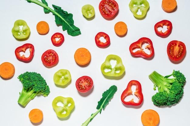 Ассорти из нарезанных овощей на белой поверхности.