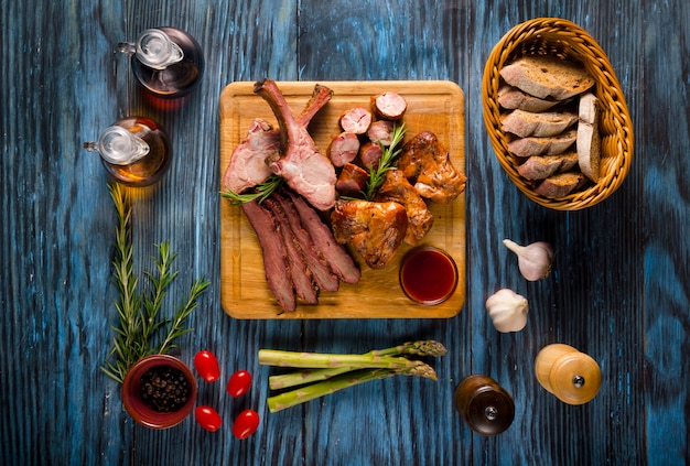 Assorted smoked meat on rustic wooden background