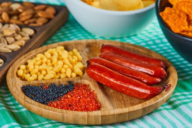 Spuntini assortiti, ciotola di patatine e un piatto di salsicce su un tavolo blu.