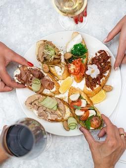 レストランまたはカフェでの各種スナックチーズ前菜硬化肉オリーブと赤白ワイン2杯