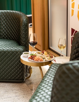 Assorted snacks. cheese appetizer, cured meats, olives with two glasses of red and white wine in restaurant or cafe.