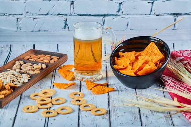 파란색 테이블에 모듬 스낵, 칩 및 맥주 한 잔.