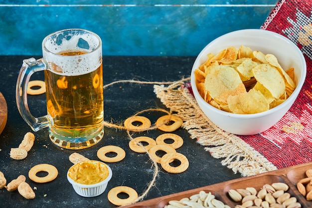Ассорти закуски, чипсы и стакан пива на темном столе.