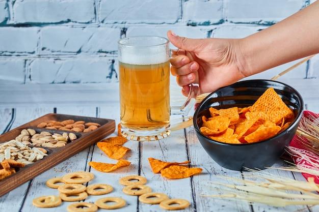 파란색 테이블에 모듬 된 스낵, 칩 및 맥주. 친구 그룹을위한 테이블.