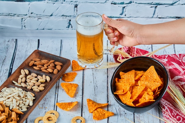 Assorted snacks, chips, and beer on blue table. table for group of friends.