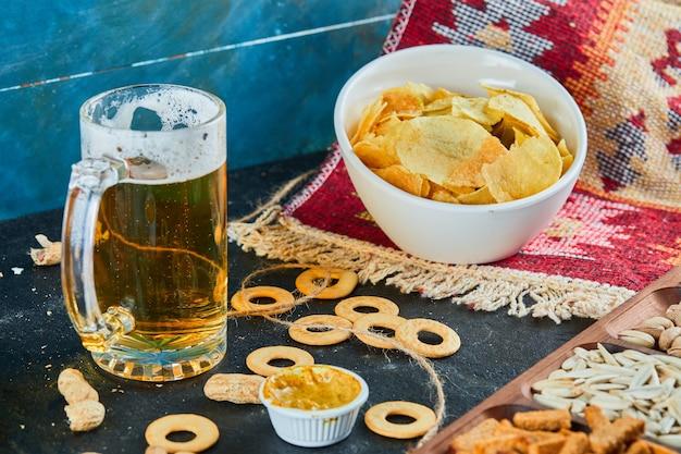 Spuntini assortiti, patatine e un bicchiere di birra sul tavolo scuro.