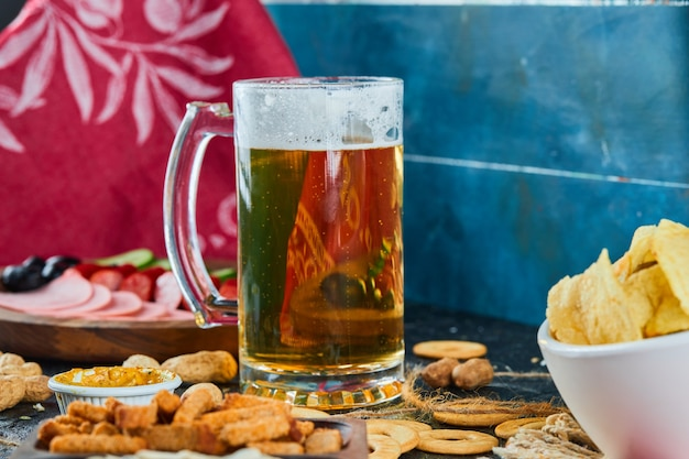 Assorted snacks, chips, a plate of sausages and a glass of beer on dark surface.