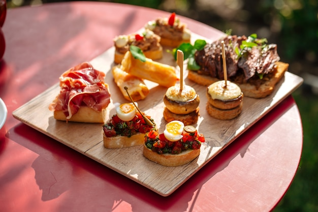Assorted spanish tapas with different toppings on the wooden board
