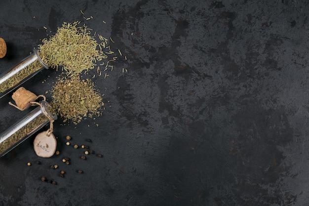 Ассорти из специй и трав на темно-черном фоне. приправы к еде. розмарин и базилик в стеклянных колбах. ингредиенты домашних специй для приготовления
