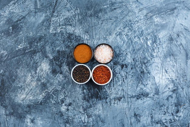 Assorted spices in small bowls on a grey plaster background. top view.