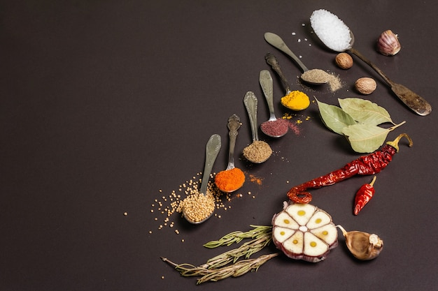 Assorted spices in spoons, dry herbs and vegetables