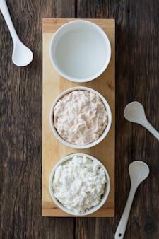 다양한 스프레드 샌드위치 파스타와 채식 스프레드는 나무 테이블에 있는 흰색 용기, 다이어트 식품, 위쪽 전망