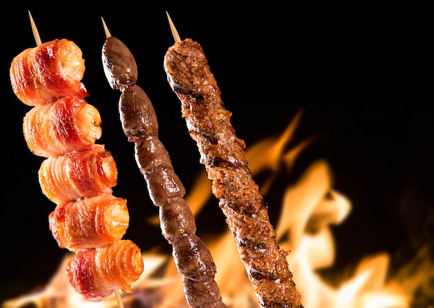 Assorted steak skewers over fire flames.