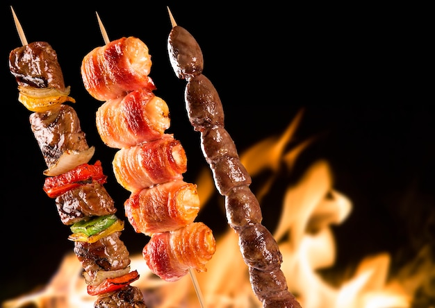 Assorted steak skewers over fire flames