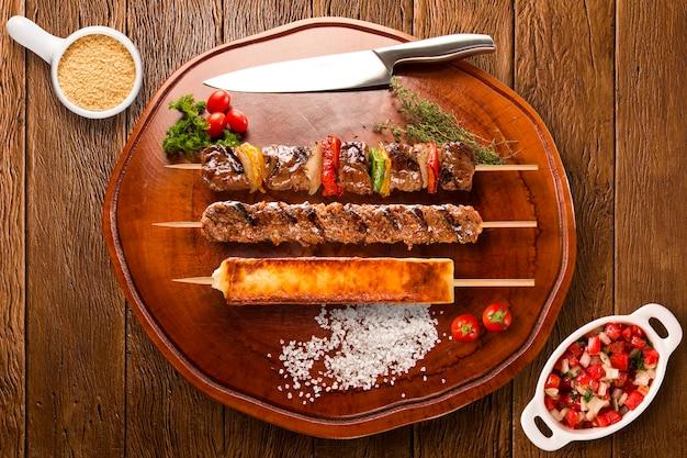 Assorted steak skewers on top of a board.