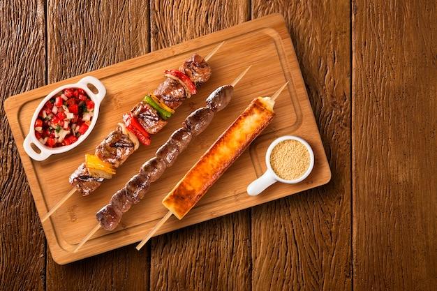 Assorted steak skewers on top of a board