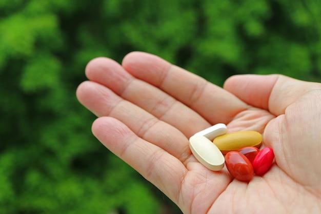 Ассорти таблетки в мужской ладони с размытой зеленой листвой