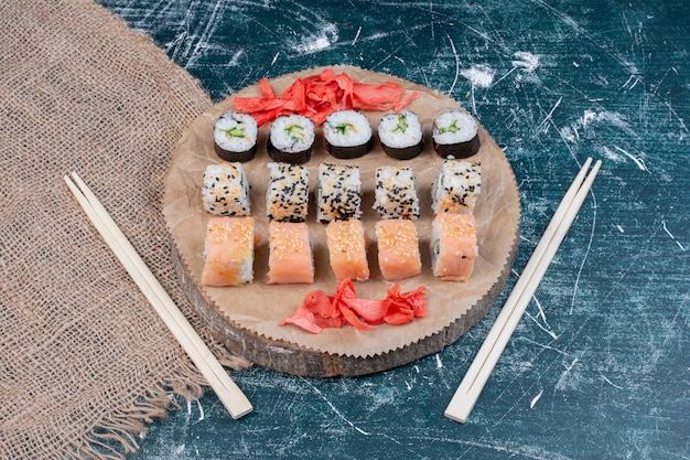 Assorted sushi rolls served on wooden platter with pickled ginger and chopsticks.