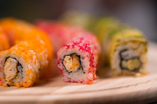 Assorted sushi rolls with fresh raw fish on a wooden board viewed close up