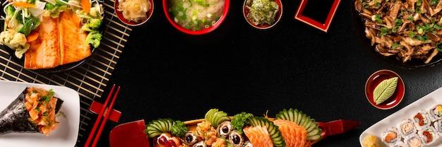 寿司セットメニューの盛り合わせ。黒背景の日本食。上面図。