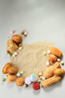 텍스트 또는 레시피를 위한 나무 테이블 중앙에 복사 공간이 있는 다양한 달콤한 구운 제품/페이스트리. 마카롱, 머랭, 마들렌, craquelin eclair, 미니 크루아상. 평면도