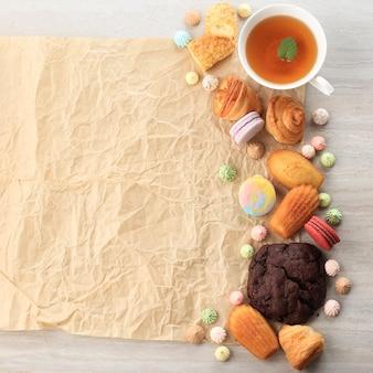 テキストまたはレシピ用の木製テーブルの中央にコピースペースがある各種の甘い焼き菓子/ペストリー。マカロン、メレンゲ、マドレーヌ、クラケリンエクレア、ミニクロワッサン。上面図