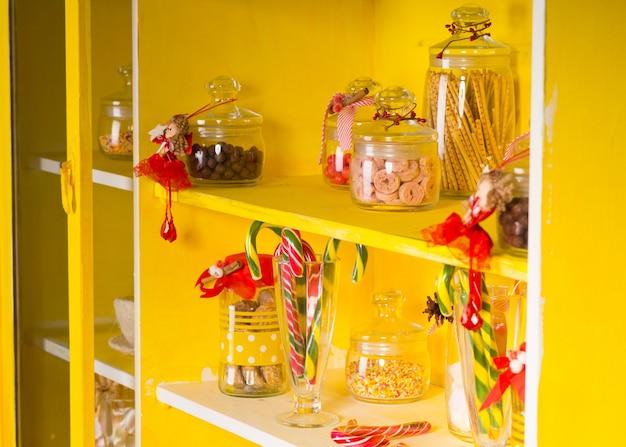 黄色い棚の透明なガラスの瓶にさまざまな甘いキャンディー