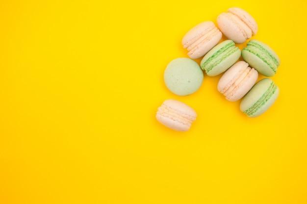黄色の背景に甘い新鮮なマカロンの盛り合わせ。フランスのデザート