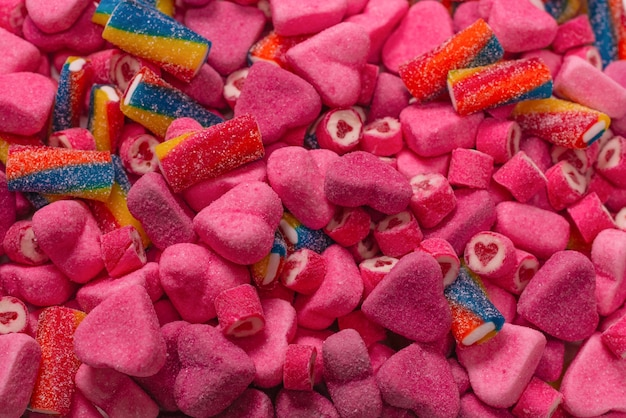 Assorted tasty gummy candies. top view. pink jelly sweets background.
