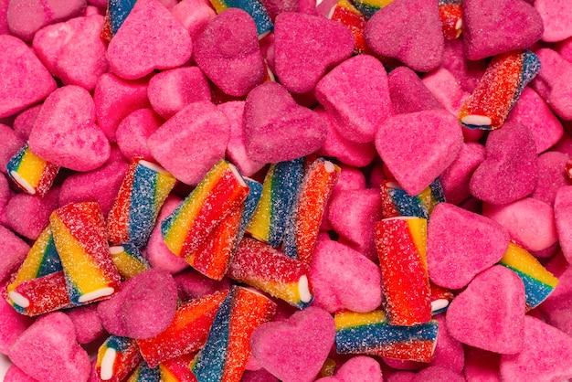 모듬된 맛있는 젤리 사탕. 평면도. 핑크 젤리 과자 배경입니다. 프리미엄 사진