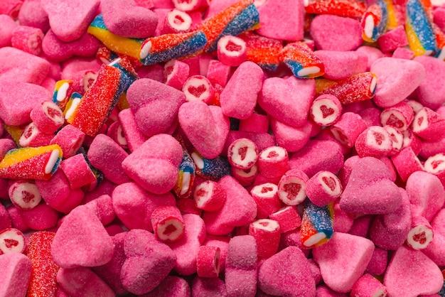 Ассорти вкусных мармеладных конфет. вид сверху. розовый фон конфеты желе.