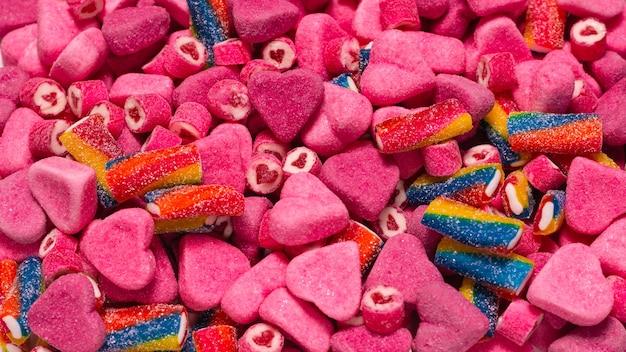 おいしいグミキャンディーの盛り合わせ。上面図。ピンクのゼリーのお菓子の背景。