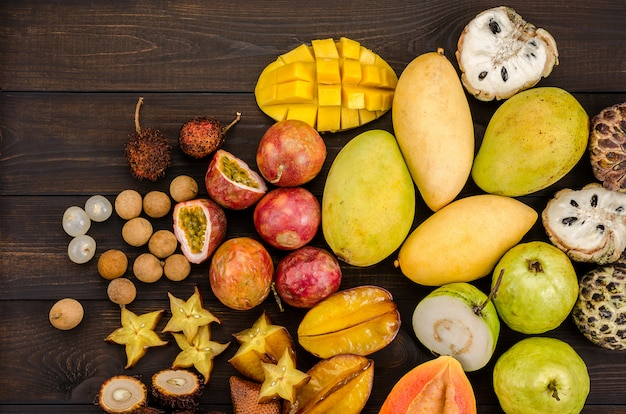 Assorted thai tropical fruits on a dark wooden rustic background.