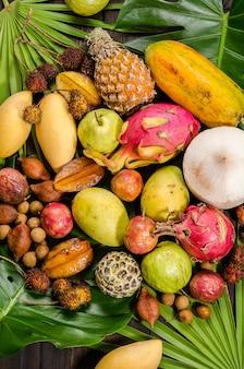 暗い木製の素朴な背景にタイの熱帯の果物の盛り合わせ。